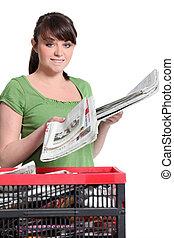 jonge vrouw , recycling, kranten