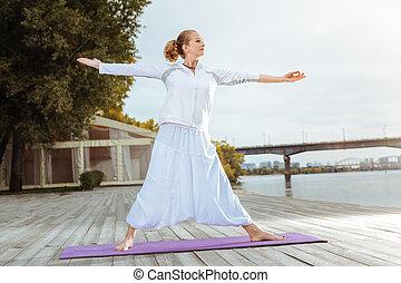 jonge vrouw , staand, in, yoga positie, terwijl, doen, morgen, oefeningen
