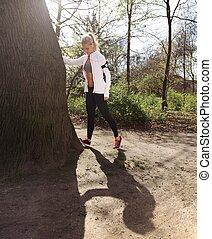 jonge vrouw , stretching, voor, een, joggen, in, bos