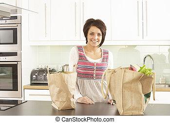 jonge vrouw , uitpakken, shoppen , in, moderne, keuken