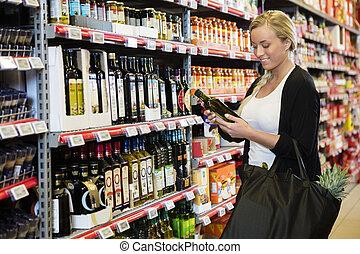 jonge vrouw , vasthouden, olijvenolie, fles, in, supermarkt