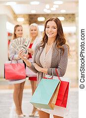 jonge vrouwen, met, het winkelen zakken, en, geld, in, mall