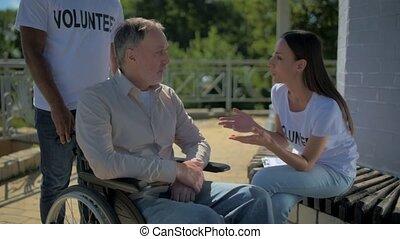 jonge, vrouwlijk, vrijwilliger, klesten, met, een, wheelchaired, man