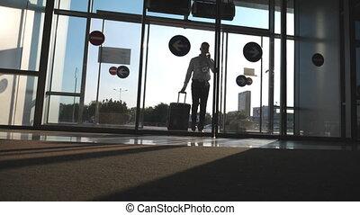 jonge, zakenman, gaan, om te, de, luchthaven, met, zijn, bagage, en, klesten, op, telefoon., man te lopen, met, suitcase., kerel, gaat, door glas, deur, en, rol, koffer, op, wheels., uitstapjes, of, reizen, concept., slowmotion