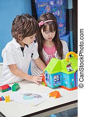jongen en meisje, spelend, met, plastic, woning, in, kleuterschool