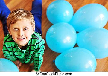 jongen, het leggen, op, de, houtenvloer, met, blauwe , ballons
