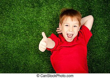jongen, het liggen, op, een, groen gazon