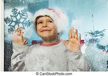 jongen, in, kerstmis hoed, achter, venster, met, snoflakes