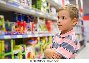 jongen, naar kijkt, planken, met, speelgoed, in, winkel