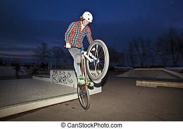 jongen, op, zijn, dirtbike, springt, op, de, skate park, door, nacht