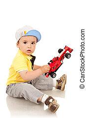 jongen, spelend, met, zijn, speelgoedauto