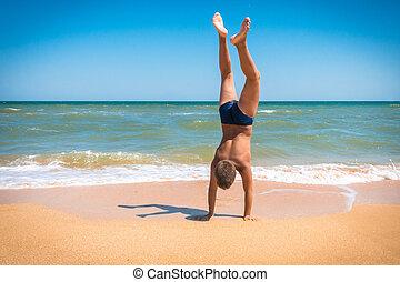 jongen, staand, ondersteboven, op het strand