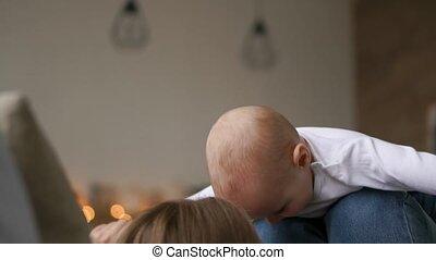 jongen, weinig; niet zo(veel), concept, mensen, op, gezin, -, feestdagen, lichten, achtergrond, moeder, baby, kussende , moederschap, vrolijke