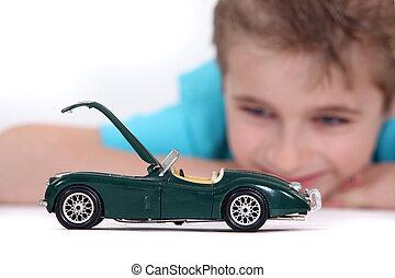 jongen, weinig; niet zo(veel), speelgoedauto, schouwend