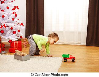 jongetje, in, kerstmis, spelend, met, nieuw, speelgoedauto