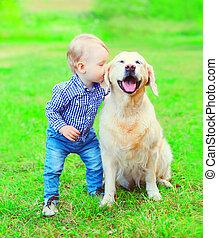 jongetje, kind, is, kussende , gouden retriever, dog, op het gras, in het park