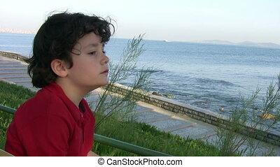 jongetje, zittende , op de bank