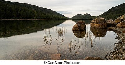 Jordan Pond with rocks and reflections and green forest at twilight