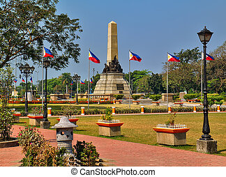 Josie Rizal Monument in Rizal Park near Manila Bay in the Philippines. There are always two soldiers on guard. The Park is very active and they have music playing out of large speakers through out the park.