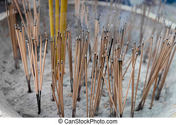 Lighted incense sticks smolder and smoke from the ashes of a Buddhist altar in a temple.