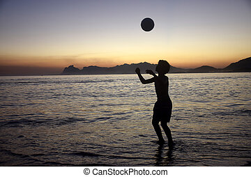 jouant football plage, coucher soleil