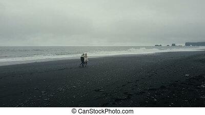 jouir de, volcanique, aérien, marche couples, iceland., jeune, touristes, courant, noir, plage, lopapeysa, waves., vue