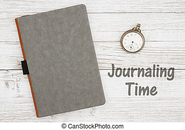 Journaling time with blank gray journal with pocket watch on a weathered whitewash wood background with copy space for your message