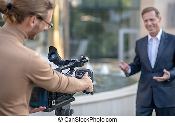 Journalistic story. Fair-haired operator filming mature male report outside