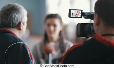 Journalists making interview with young woman