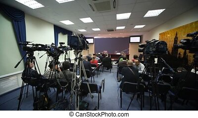 Journalists wait conference in press room, cameras and other equipment stand around