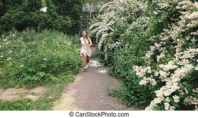 Journey. Young happy woman is jumping and running in the park.
