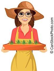 jovem, agricultor, mulher, com, óculos, segurando um cofre, de, fresco, verde, seedlings, plantas