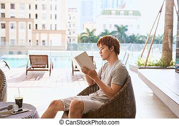 jovem, asian tripulam, livro leitura, por, a, piscina, ligado, um, ensolarado, dia verão