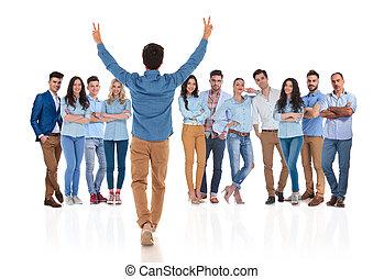 jovem, casual, homem, felicita, seu, colegas, com, mãos cima