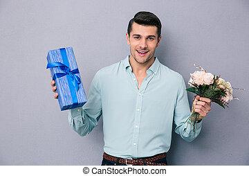 jovem, casual, homem, segurando, caixa presente, e, flores