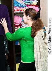 jovem, caucasiano, mulher, em, a, guarda-roupa, pacotes, coisas, ligado, um, shelfs.