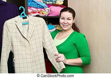 jovem, caucasiano, mulher segura, um, mala, e, ficar, perto, a, wardrobe., embalagem, coisas, em, um, shelves.