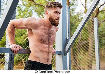 jovem, concentrado, barbudo, homem forte, fazendo, esportes, exercícios