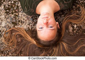 jovem, cute, na moda, menina, mentindo, ligado, um, pedra, fundo, com, disperso, através, a, hair.