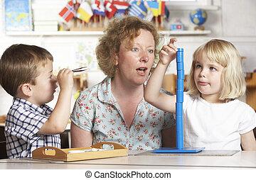 jovem, dois, ajudando, crianças adultas, montessori/pre-school