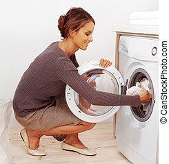 jovem, dona de casa, fazendo lavanderia