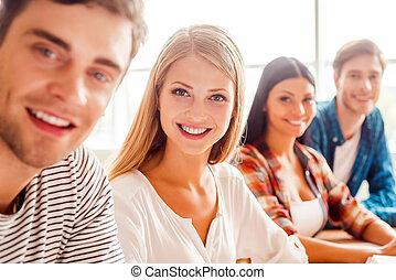 jovem, e, beautiful., grupo, de, feliz, jovens, olhando câmera, e, sorrindo, enquanto, sentando, uma fileira, em, a, sala aula