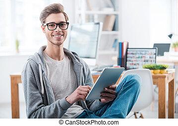 jovem, e, confiante, professional., feliz, homem jovem, trabalhar, laptop, e, sorrindo, câmera, enquanto, sentando, em, escritório