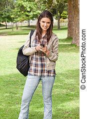 jovem, estudante, posar, enquanto, usando, um, smartphone