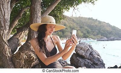 jovem, excitado, mulher, em, swimsuit, e, fabricação chapéu, selfie, disparar, usando, smartphone, durante, férias, ligado, praia
