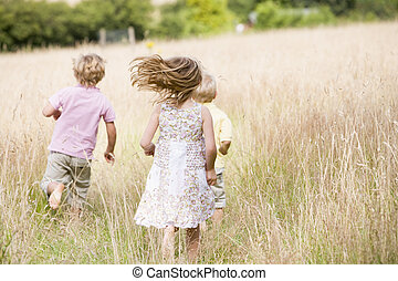 jovem, executando, três crianças, ao ar livre