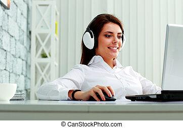 jovem, executiva, em, fones, trabalhar, um, laptop, em, escritório
