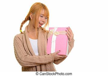 jovem, feliz, mulher asian, sorrindo, enquanto, segurando,...