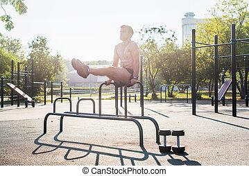 jovem, forte, atleta, trabalhar, em, ao ar livre, ginásio, fazendo, perna, levantamento, abs, exercise.