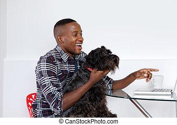 jovem, homem africano, mostrando, algo, ligado, laptop, para, seu, animal estimação, cão